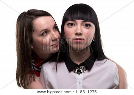 Two young brunette women - serious and smiling