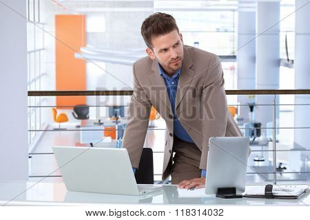 Serious caucasian businessman working with laptop and tablet at startup office desk, upstairs. Determined, standing, leaning on table, in the business.