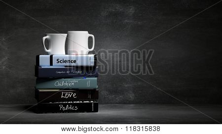 Stack of books with various subjects and two cups of coffee, with blackboard background.