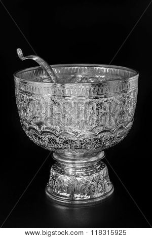 Antique silver Thai bowl on tray with pedestal and ladle on black background
