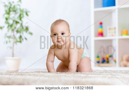 happy baby child smiling and crawling on floor in nursery