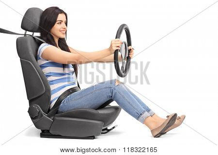 Young woman sitting on a car seat and holding a steering wheel isolated on white background