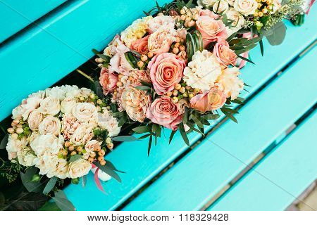 Bride And Bridesmaids Wedding Bouquets With Roses And Other Flowers On Turquoise Bench
