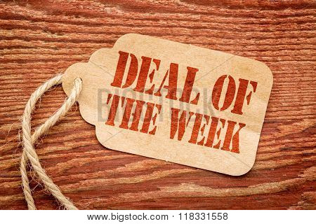 deal of the week sign a paper price tag against rustic red painted barn wood