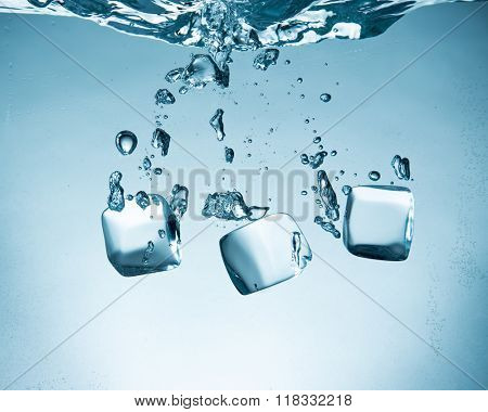 Ice cubes splashing into water, close-up