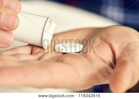 closeup of a young caucasian man in pajamas in bed about to take a tablet from a tube