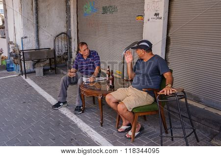 Conversation in the shade over beer