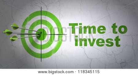 Time concept: target and Time To Invest on wall background