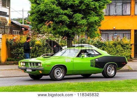 TEMUCO CHILE - NOVEMBER 22 2015: Green motor car Dodge Challenger drives in the town street.