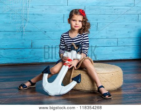 Child Sitting And Holding An Anchor