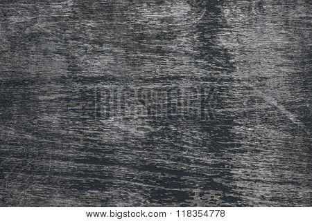Background of dark weathered wood texture with peeling black paint showing grey woodgrain