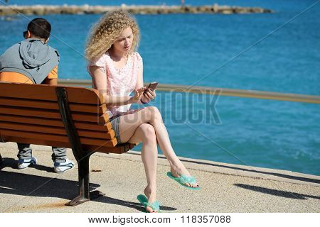 Woman With Phone On Bench