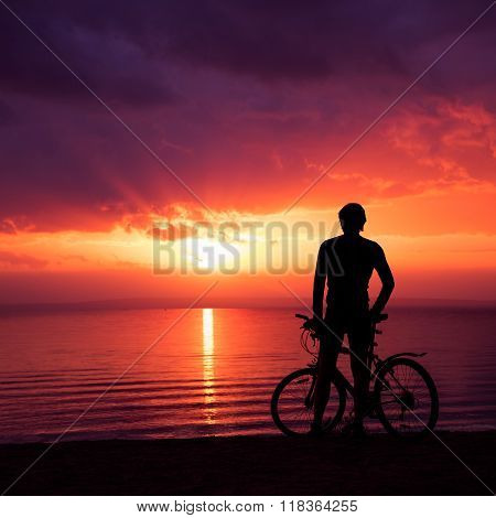 Man Standing with a Bike at Sunset by the Sea