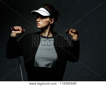 Fit Woman Workout With Resistance Band Against Dark Background