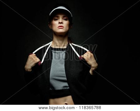 Woman Athlete Holding Resistance Band Against Black Background