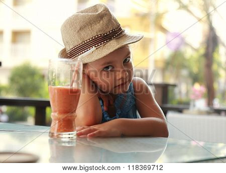 Cute Unhappy Kid Sitting In Restaurant And Not Want To Drink Healthy Juice On Summer Background