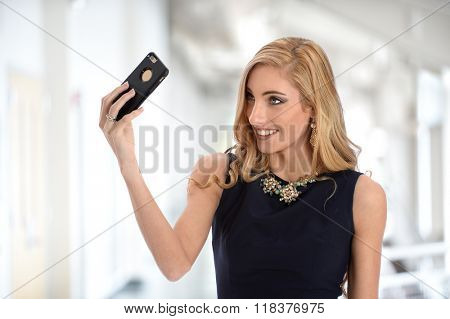 Portrait of young businesswoman talking selfie with mobile phone inside office building