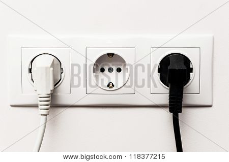 Triple Electrical Socket With Two Plugged Cables.