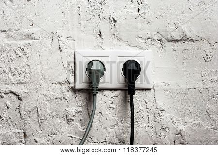 Double Electrical Socket With Plugged Cables.