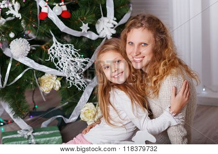 Portrait Of Happy Smiling Little Girl With Mother Sitting Near Christmas Tree.