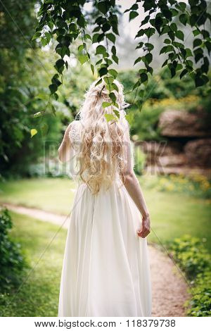 Bride with long fair hair from back in the garden