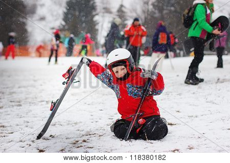 Little Cute Boy With Skis And A Ski Outfit. Little Skier In The Ski Resort.