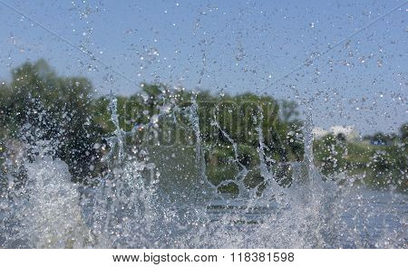 Water spray on the background of trees.