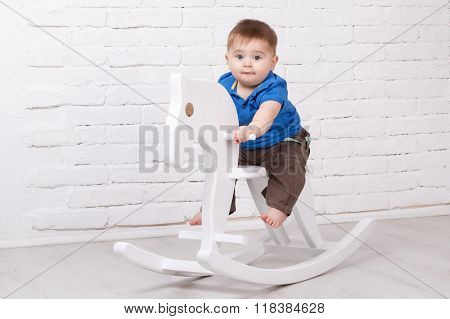 Funny baby sitting on the toy horse