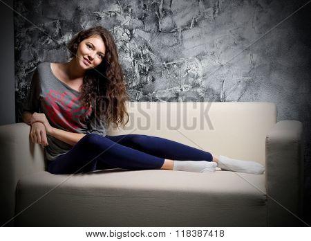 Young girl on sofa at grey wall