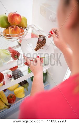 Close up young woman on diet stealing from fridge piece of nice chocolate cake