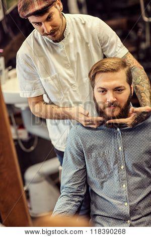skillful barber making haircut too bearded customer at barbershop
