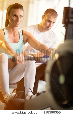Gym woman with supervision of a personal trainer doing exercise at the gym