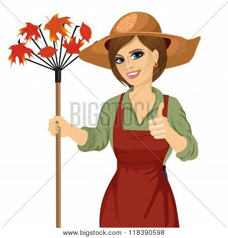 Woman with garden hat holding rake