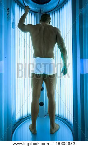Young man have tanning skin treatment in modern solarium