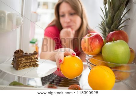 Woman hesitating whether to eat piece of chocolate cake or orange