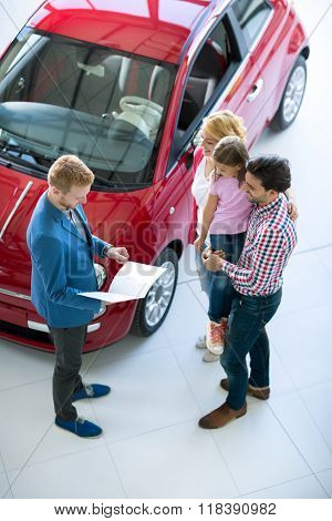 Young family with car dealer in car dealership saloon