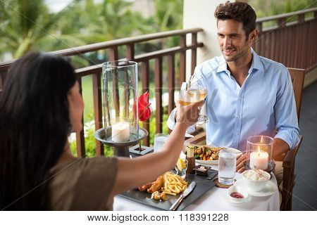 Affectionate couple having dinner on the balcony tropical resort