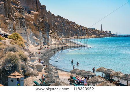 People swimming and sunbathing at beach near white rocks of Vlychada town of Santorini island