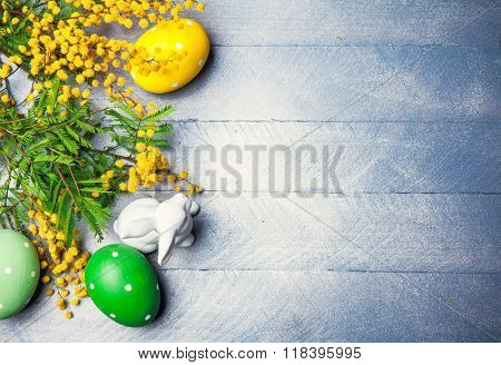 Easter festive still life with branch mimosa eggs and rabbit on blue wooden board