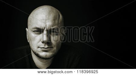 Black and white portrait of a bald man moody