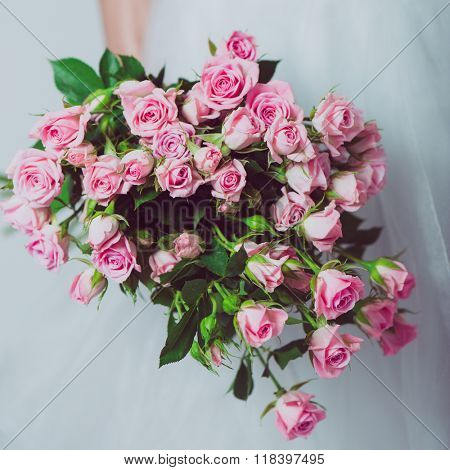 Wedding bouquet of flowers, young bride holding a bouquet of pink roses. Image of wedding dress and pink bouquet.