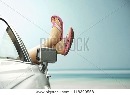 Woman's legs showing from a vintage convertible