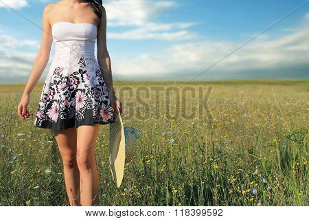 Woman relaxing outdoors, taking a walk on a meadow