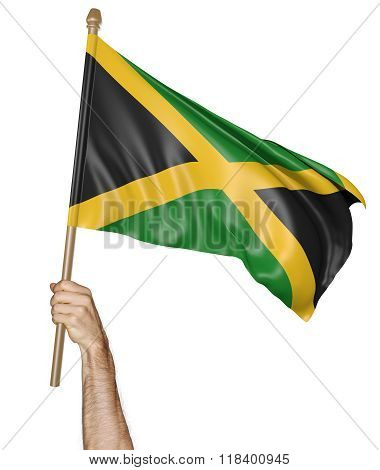 Hand proudly waving the national flag of Jamaica