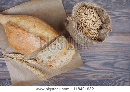 Fresh baked wheaten bread on wooden background with grains