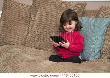 Young girl sitting on sofa laughs at tablet screen