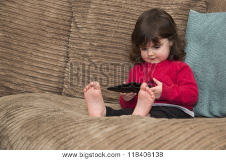 Toddler uses tablet PC witting on sofa