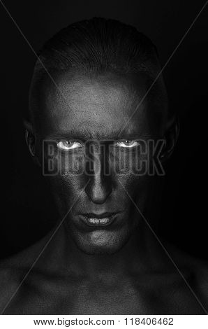 Gothic And Halloween Theme: A Man With Black Skin Is Isolated On A Black Background In The Studio, T