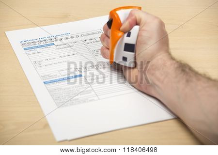Male hand squeezing a stress ball house over mortgage papers