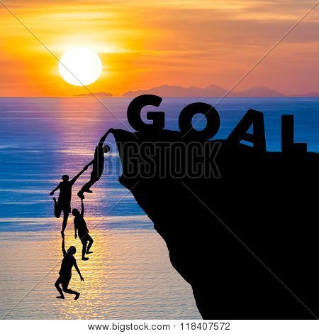 Silhouette teamwork of people climbs into cliff to reach the word GOAL with sunrise (goal setting business concept)